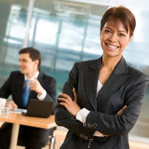 woman standing in front of man sitting at desk talking to another person