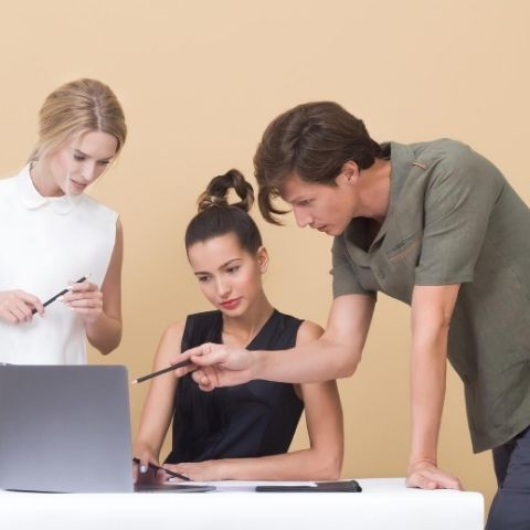 Man and two women reviewing task in front of computer