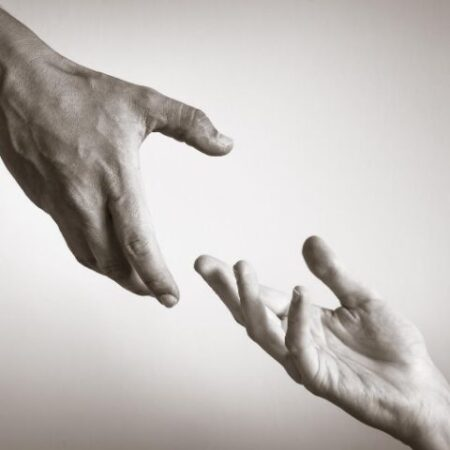 One hand reaching for another hand