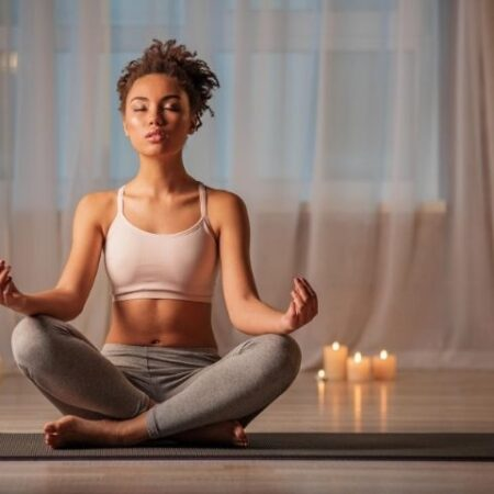 Woman meditating while sitting on floor
